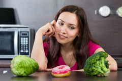 Woman chooses what to eat vegetables or a cake Royalty Free Stock Photo