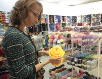 A woman chooses the yarn in the store. A woman makes a purchase yellow yarn for knitting in the store. stock photo