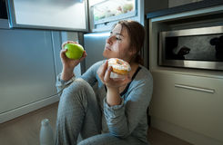 Woman choosing between apple and donut at evening lunch Royalty Free Stock Photos
