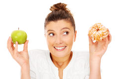 Woman choosing between apple and donut Stock Image