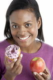 Woman Choosing Between Apple And Doughnut stock image