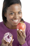 Woman Choosing Between Apple And Doughnut Stock Images