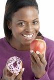 Woman Choosing Between Apple And Doughnut stock images