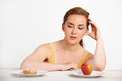 Woman Choosing Between Apple And Doughnut For Snack Stock Images