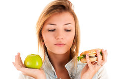 Woman choosing between apple and hamburger Stock Photos