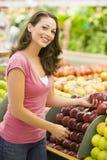 Woman choosing apples at produce counter royalty free stock photo