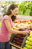 Woman choosing apples in produce department Stock Photography