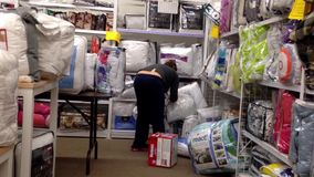 Woman choosing a bedquilt inside home outfitters store stock video