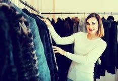 Woman choosing best fur coat in women's cloths store Royalty Free Stock Images