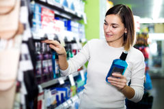 Woman choosing best mouthwash. Smiling young woman choosing best mouthwash in supermarket Royalty Free Stock Photography
