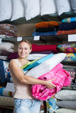 Woman choosing blanket and pillow. Portrait of woman choosing blanket, pillow and textile in bedding section in shop Royalty Free Stock Photo