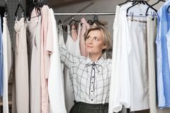 Woman choosing blouses from ranks. At store stock photography