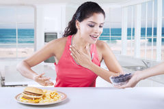 Woman choosing between blueberry or hamburger Stock Image