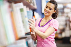 Woman choosing book. Young woman choosing a book in bookstore Royalty Free Stock Images