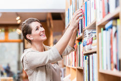 Woman choosing book in bookstore Stock Photography