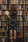 A woman is choosing a book in a bookstore in Ho Chi Minh City, Vietnam on February 2017 stock images