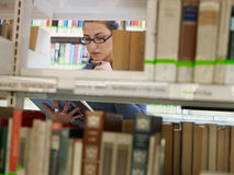 Woman choosing book in library Royalty Free Stock Images