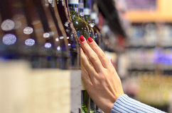 Woman choosing a bottle of wine off the shelf. In a supermarket with a close up oblique angle view down the row of bottles Royalty Free Stock Image