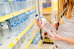Woman choosing bottled mineral water. In supermarket store royalty free stock image