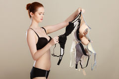 Woman choosing bras to wear. Bosom concept. Slim attractive red hair woman wearing black underwear holding many bras in hand, choosing witch bra to wear Royalty Free Stock Photo