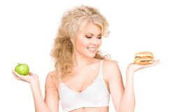 Woman choosing between burger and apple Royalty Free Stock Photos