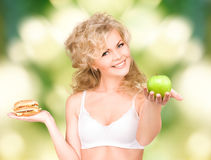 Woman choosing between burger and apple Stock Photography