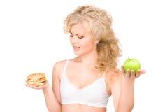 Woman choosing between burger and apple Stock Photos