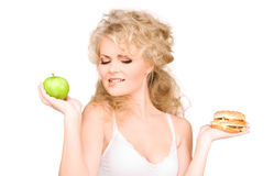 Woman choosing between burger and apple Royalty Free Stock Image