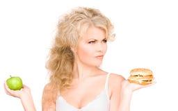 Woman choosing between burger and apple Royalty Free Stock Photos