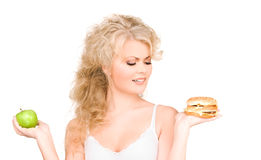 Woman choosing between burger and apple Stock Photos