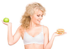 Woman choosing between burger and apple Royalty Free Stock Photo