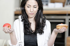 Woman choosing cake or fruit Royalty Free Stock Photos