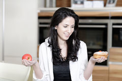 Woman choosing cake or fruit Stock Photos