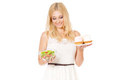 Woman choosing cake and salad Stock Images