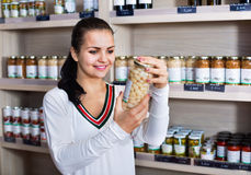 Woman choosing canned beans in grocery shop. Smiling woman choosing canned beans in grocery shop Royalty Free Stock Image