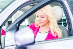 Woman choosing car for buying. In dealership Royalty Free Stock Photos