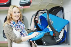 Woman choosing child car seat. For newborn baby in shop supermarket Stock Image