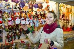 Woman choosing Christmas decoration at market in evening time Stock Image