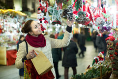 Woman choosing Christmas decoration at market in evening time Royalty Free Stock Photos