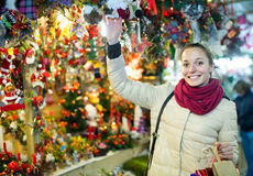 Woman choosing Christmas decoration at market in evening time Stock Photos