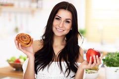 Woman Choosing Between Cinnamon Roll And Apple. Picture of Woman Choosing Between Cinnamon Roll And Apple Royalty Free Stock Images