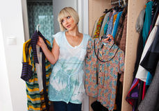 Woman choosing clothes. In front of full closet Stock Photos