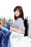 Woman choosing clothes. Young beautiful woman choosing clothes for itself Stock Photos