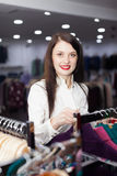 Woman choosing clothes at clothing store Stock Image