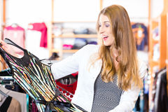 Woman choosing clothes in fashion shop Stock Photography