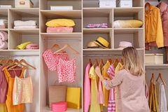 Woman choosing clothes from large wardrobe. Closet stock image