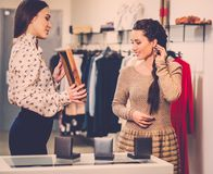 Woman choosing clothes with shop assistant Stock Photo