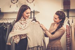 Woman choosing clothes with shop assistant. Young women choosing clothes on a rack in a showroom Stock Image
