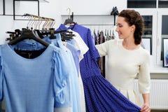 Woman choosing clothes in a shop Stock Photos