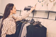 Woman choosing clothes in a showroom Stock Image